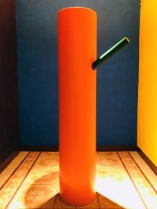 """<span class=""""nome_artista"""">Andreas Waldmeier<p class=""""nome_opera"""">Baumstamm</p><p class=""""info_opera"""">pittura su acciaio inossidabile+tinta e neon color<br>2019, h 170cm diam 35cm + cm 36,5 diam 5,8 cm"""